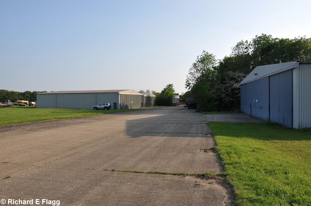 006Taxiway at the west of the airfield. Looking south west at one of the old dispersals, now where the club hangars are - 18 May 2014.png
